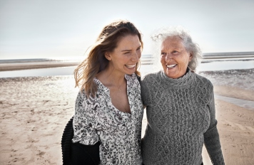 Happy senior woman with her adult daughter on the beach