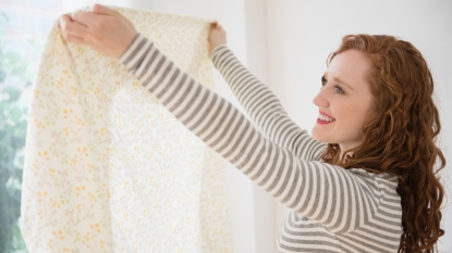 Woman holding fitted sheet