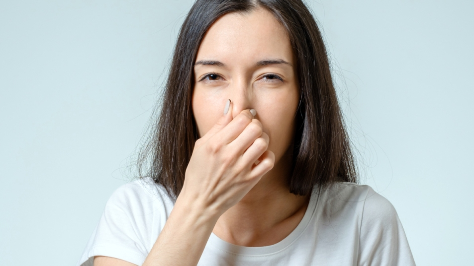 Woman pinching her nose closed