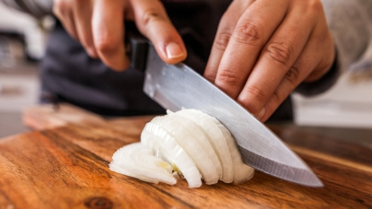 Hands cutting a white onion
