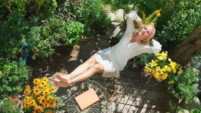 Blonde woman stretched out in her yard surrounded by greenery
