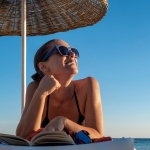 woman is reading book on the sunbed on the beach