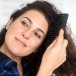 Woman combing her long, brown curly hair