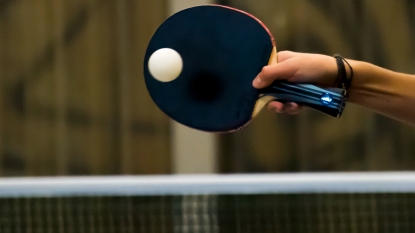 Woman's hand hitting ping pong ball with paddle