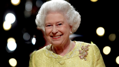 Queen Elizabeth smiling in yellow dress
