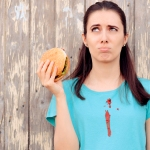 Woman holding burger with ketchup stain on blue shirt