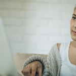 woman looking at laptop feeling worried