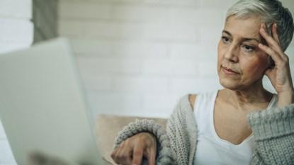woman looking at laptop feeling worried