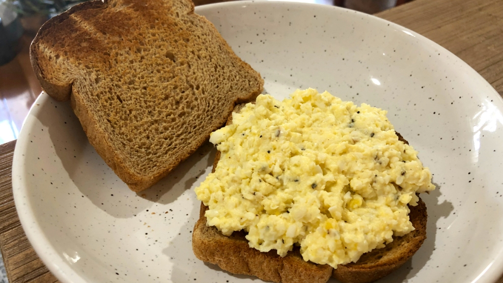 Plate with toasted bread with egg salad on top