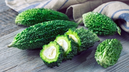 Whole and sliced karela, also known as bitter melon