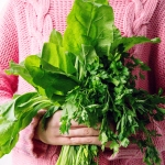 Woman in pink sweater holding leafy greens