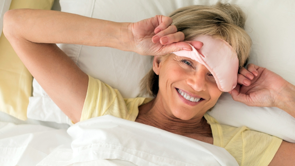 Woman lifting sleep mask off in bed