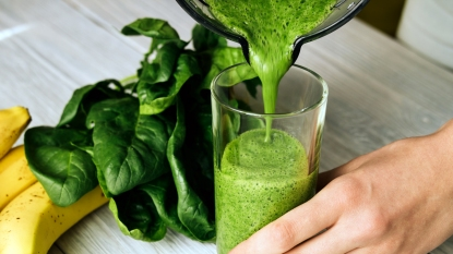 Woman pouring green smoothie