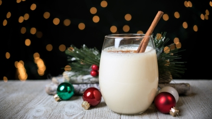 Glass of eggnog with cinnamon stick and Christmas ornaments