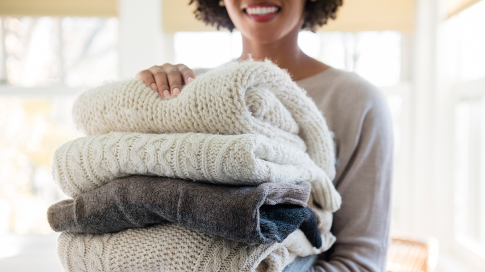 Woman Holding a Pile of Sweaters