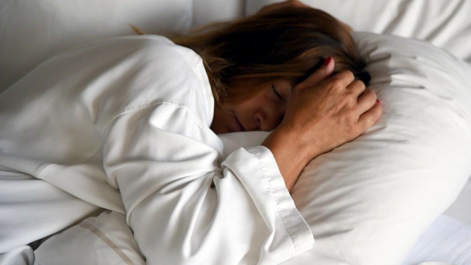 Woman asleep on white sheets