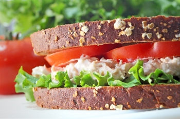 Tuna fish sandwich on whole grain wheat bread with lettuce and tomato.