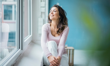 Happy woman sitting beside window sill looking out of window