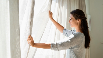 Woman Closing Curtains