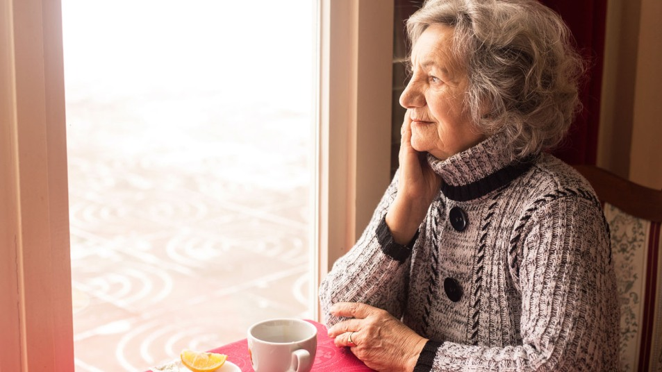 woman with the winter blues looking out a window