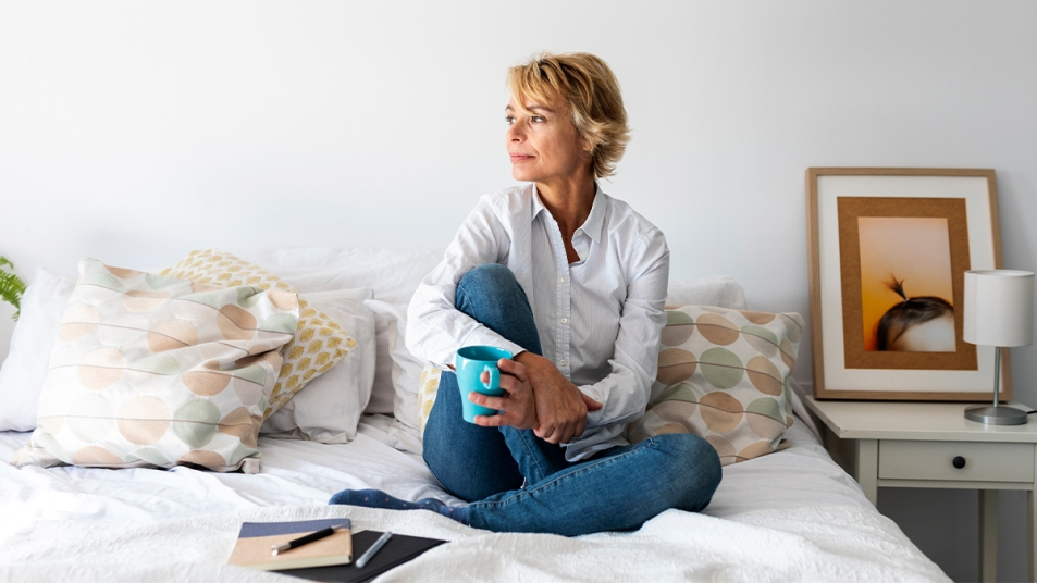 Woman sitting on her bed