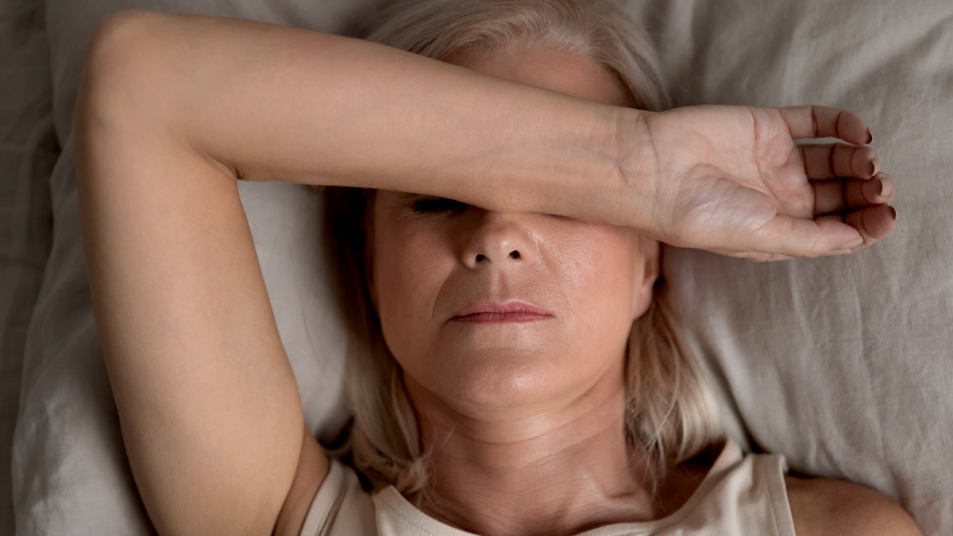 Woman in bed covering her eyes