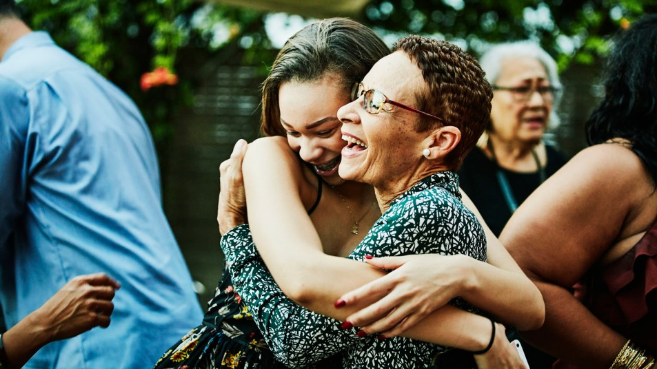 woman hugging niece at outdoor family gathering