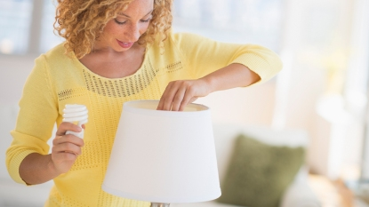 Woman changing lightbulb from lap