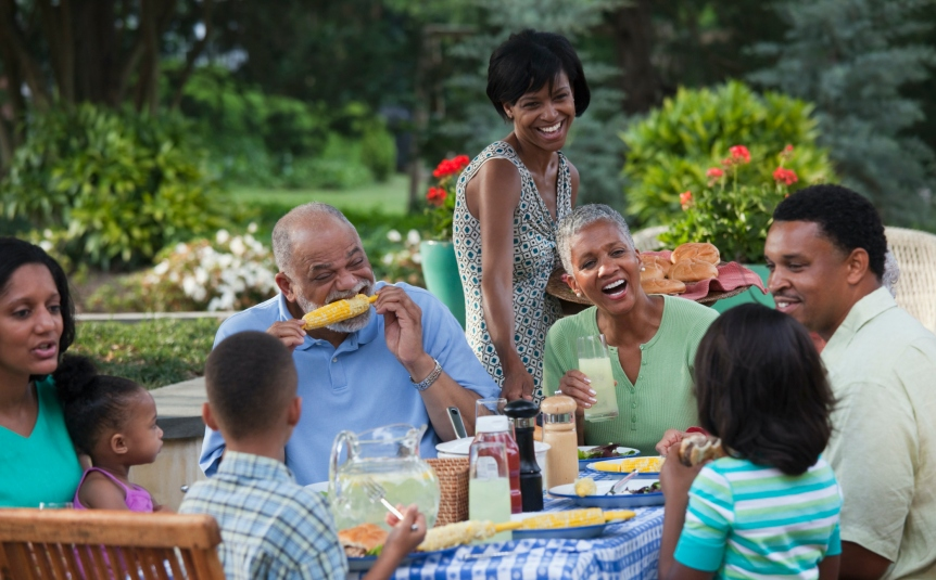 Multi-generation Black family eating at barbecue in back yard