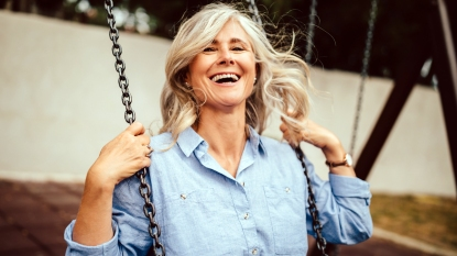 Older woman laughing on a swing