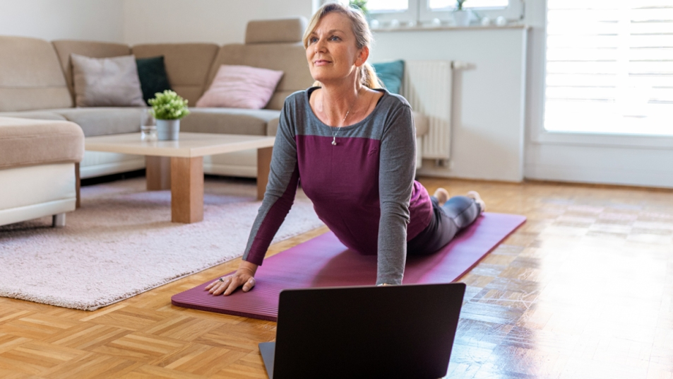 Woman stretching with laptop in front of her