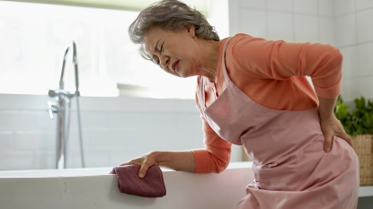 Woman with backache while cleaning