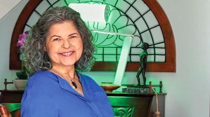 Deb Samuels sitting in front of green light lamp