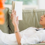 woman reading a book alone on a sofa