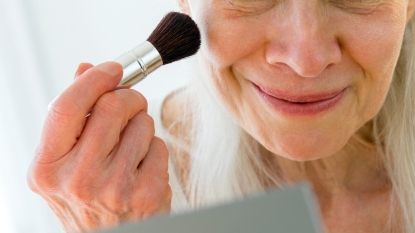 Senior woman applying makeup