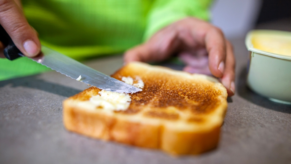 Woman's hands buttering white toast