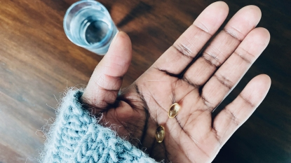 Close-up of woman's hand holding Vitamin D supplements