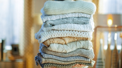 woman holding a pile of fall wardrobe sweaters