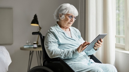 woman in wheelchair using an ipad to connect with loved ones