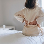 woman who needs pain relief for her sore back in the morning