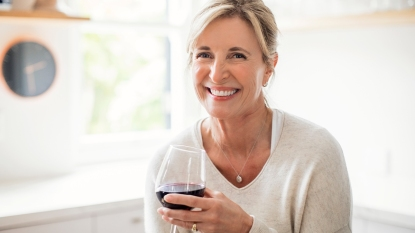 Woman smiling while holding a glass of wine