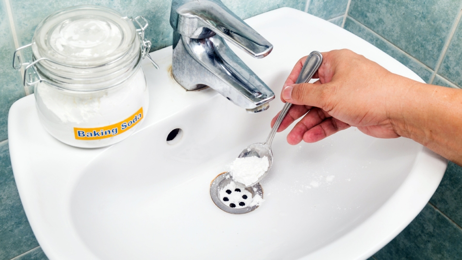Hand putting baking soda in sink