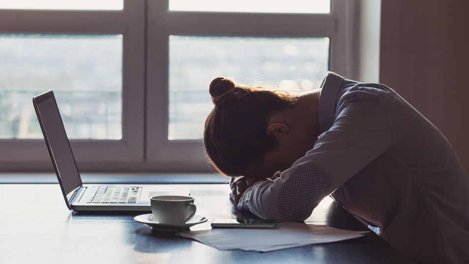 woman with her head down in front of computer
