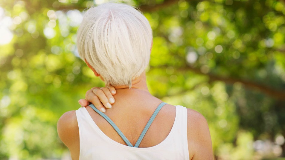woman rubbing her neck in pain with spring trees