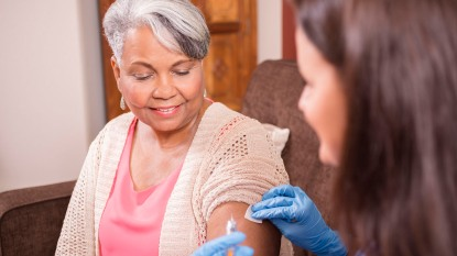 Home healthcare nurse giving covid vaccine to senior adult woman.