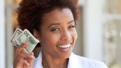 woman holding cash she saved