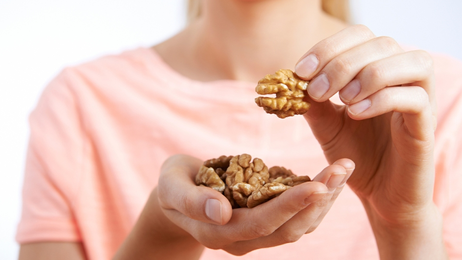 Woman with a handful of walnuts
