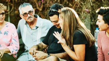 Smiling multigenerational family hanging out together during backyard barbecue