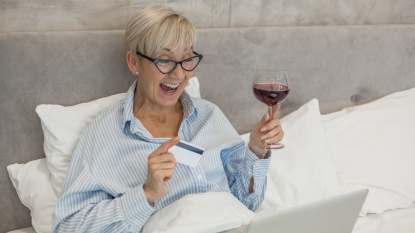 woman drinking wine and online shopping in bed