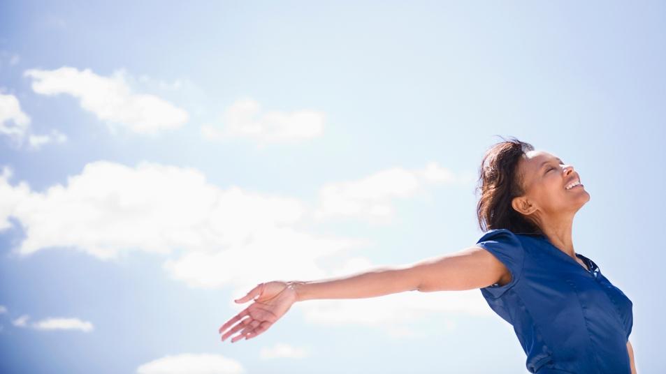 woman feeling happy outdoors blue sky